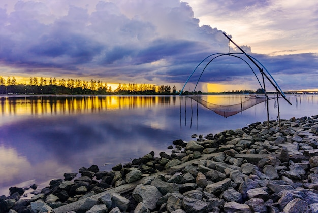 Coucher de soleil sur la mer ou le lever du soleil avec la campagne de l'outil de pêche et coloré du ciel au crépuscule
