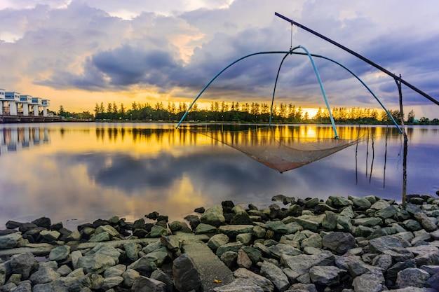 Coucher de soleil de la mer ou lever de soleil avec l'outil de pêche et coloré du ciel et des nuages au crépuscule