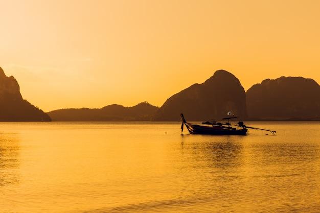 Coucher de soleil sur la mer océan calme avec la silhouette du bateau de pêche et paysage de montagne
