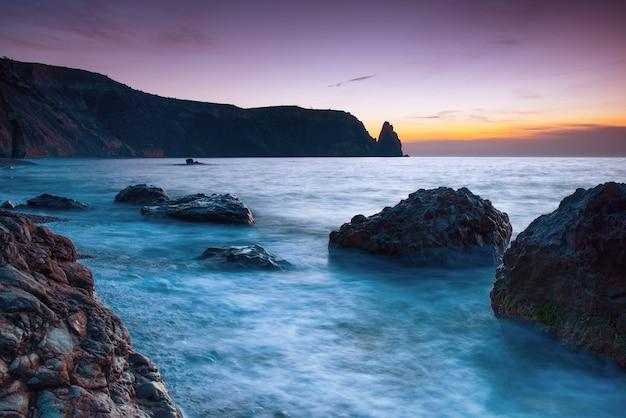 Coucher de soleil sur la mer sur la plage avec des rochers et un ciel dramatique