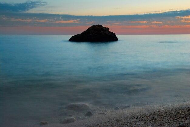 Coucher de soleil sur la mer avec de la roche et de l'eau brumeuse
