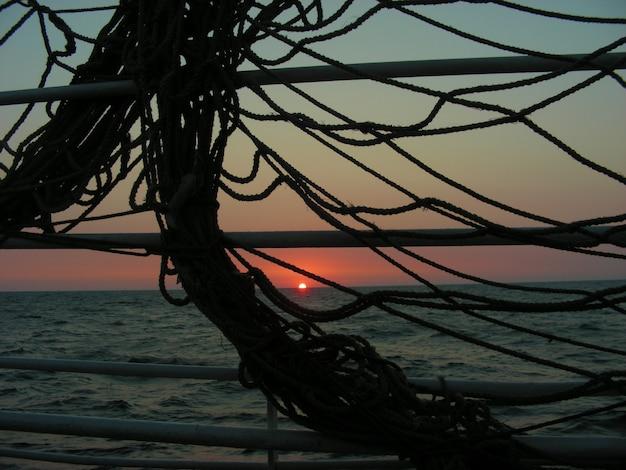 Coucher de soleil sur la mer. vue à travers les filets marins au coucher du soleil