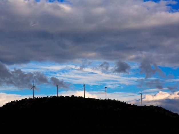 Coucher de soleil montagne avec des moulins à vent électriques