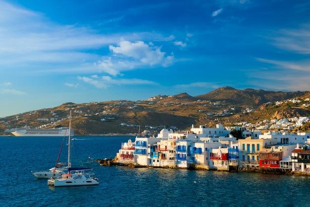 Coucher de soleil à mykonos en grèce avec bateau de croisière et yachts dans le port