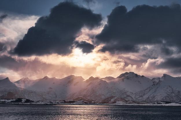 Coucher de soleil nuageux sur la chaîne de montagnes enneigées dans l'île de senja, norvège