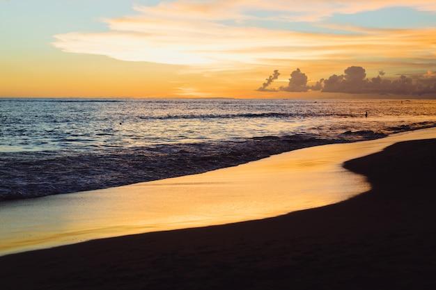 Coucher de soleil sur l'océan. beau ciel lumineux, reflet dans l'eau, vagues.