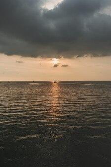 Coucher de soleil océan avec nuage orageux dans le ciel