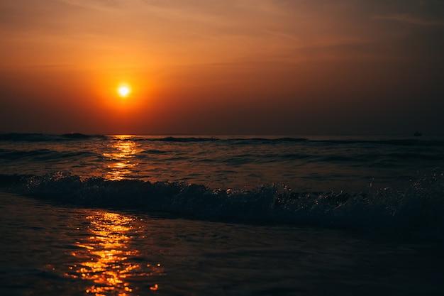 Coucher de soleil orange contre la mer avec des vagues en été sur la plage