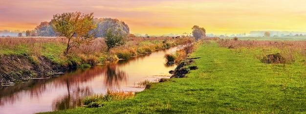 Coucher de soleil pittoresque sur une rivière étroite dans un champ sauvage