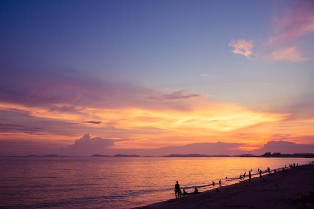 Coucher de soleil plage et ciel crépusculaire avec silhouette détente des touristes