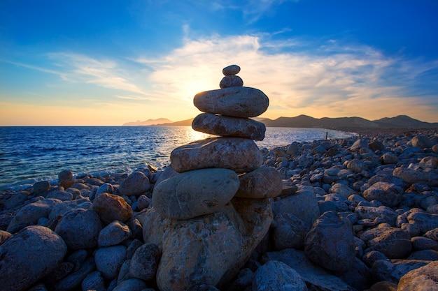 Coucher de soleil sur la plage d'ibiza cap des falco avec des pierres de désir
