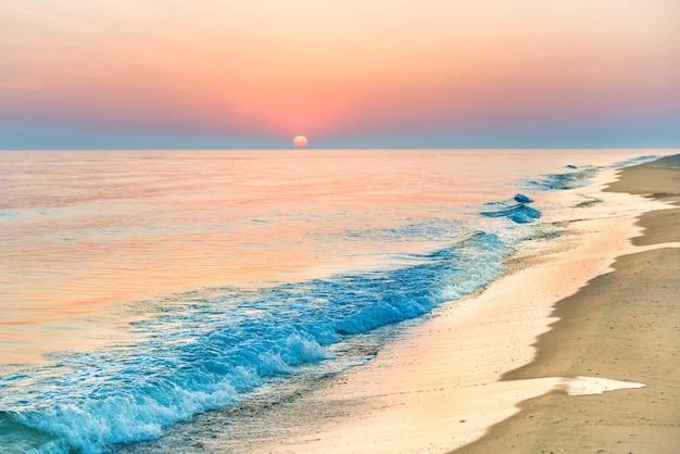 Coucher de soleil sur la plage avec longue côte, soleil et ciel dramatique