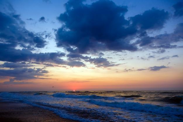 Coucher de soleil sur une plage mer agitée, ciel nuageux.
