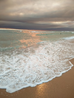 Coucher de soleil sur la plage avec des nuages sombres sur vilamoura, portugal.