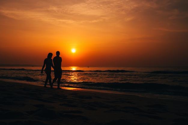 Coucher de soleil à la plage avec la silhouette du couple