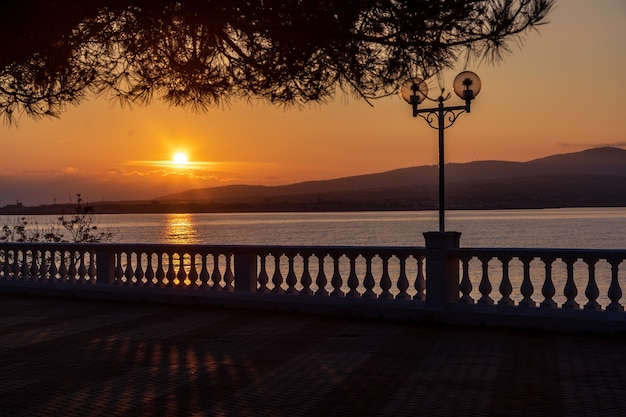 Coucher de soleil sur le quai du complexe avec balustrade et lanternes. le soleil se couche dans les montagnes et se reflète dans la mer. branche de pin.la station balnéaire de gelendzhik.