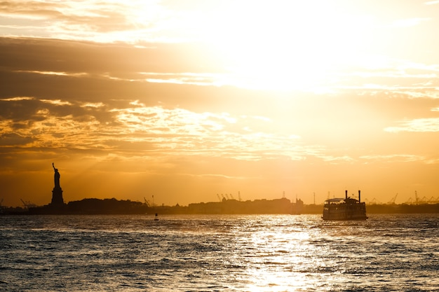 Coucher de soleil sur la rivière hudson et la statue de la liberté