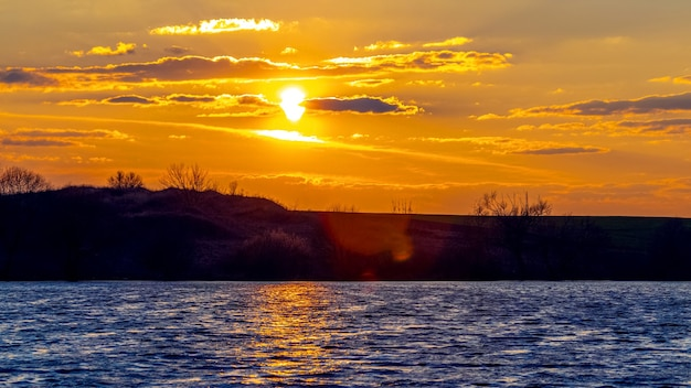 Coucher de soleil sur la rivière, vagues sur l'eau et reflet du soleil