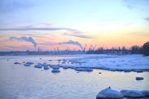 Coucher de soleil rose d'hiver et vue sur le paysage urbain au bord de la mer baltique. coucher de soleil avec rochers enneigés et paysage de plage. mer baltique, heure d'hiver
