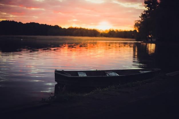 Coucher de soleil rose sur le lac avec un vieux bateau. arrière-plan naturel flou, ciel coucher de soleil sur le lac. baner nature silhouette