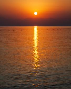 Coucher de soleil rouge en mer sur les montagnes