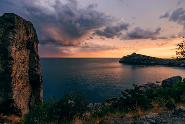 Coucher de soleil rouge orange contre le bleu de la mer et des montagnes