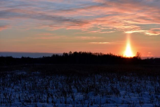 Coucher de soleil rouge vif dans le domaine d'hiver