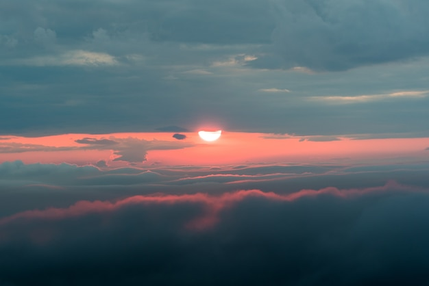 Coucher de soleil avec un soleil rouge et des nuages