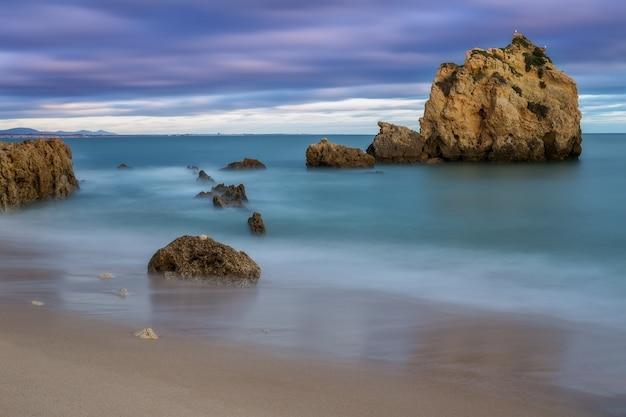 Coucher de soleil spectaculaire sur la mer. vagues floues et nuages.