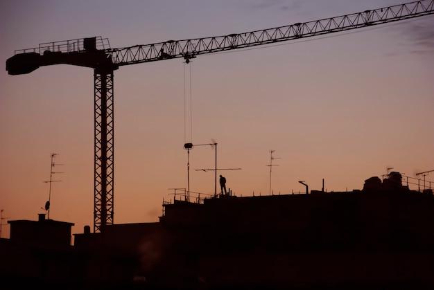 Coucher de soleil sur le toit avec la silhouette d'un ouvrier et une grue de construction