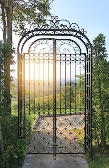Coucher de soleil à travers les barreaux de la porte en fer forgé à flanc de colline.