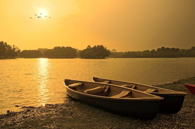 Coucher de soleil et vieux bateau de pêche en bois près de la rive du lac d'été