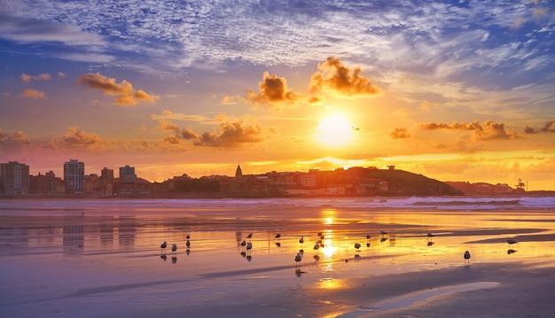 Coucher de soleil sur la ville de gijon sur la plage de san lorenzo, asturies