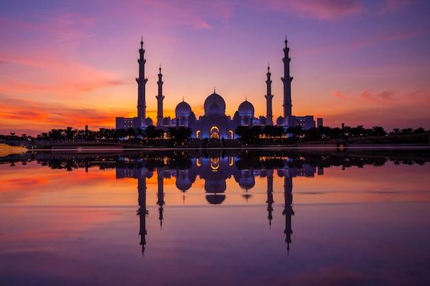 Coucher de soleil violet magique de la grande mosquée d'abu dhabi le soir au coucher du soleil. panorama de l'extérieur de la mosquée sheikh zayed aux émirats arabes unis.