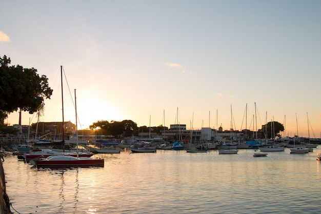 Coucher de soleil avec des voiliers ancrés au bord de la ribeira à salvador bahia au brésil.