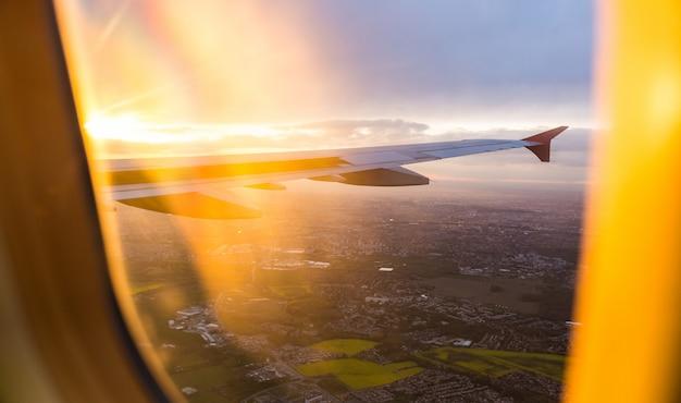 Coucher de soleil vue aérienne à travers la fenêtre de l'avion au-dessus de l'aile