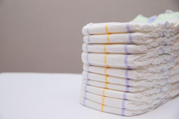 Couches pour bébé dans une pile sur un fond blanc. hygiène du bébé.