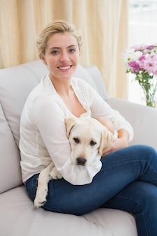 Coucou blonde heureuse avec chiot sur le canapé