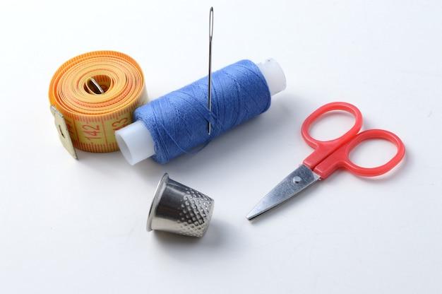 Dé à coudre, aiguille avec bobine de fil, ciseaux et ruban à mesurer .gros plan.