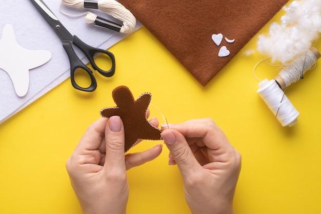 Coudre deux morceaux de bonhomme en pain d'épice en feutre avec un point de boutonnière. instruction étape par étape. étape 5.