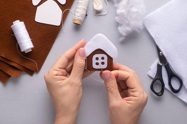 Coudre ensemble deux morceaux de maison en pain d'épice de noël en feutre.