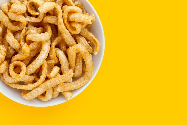 Couennes de porc croustillantes frites dans une assiette blanche sur fond jaune.