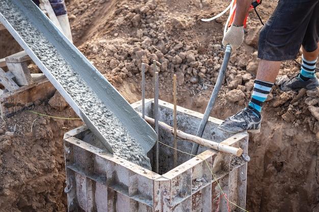 Coulage du béton dans une boîte en acier pour un pilier de fondation en cours de construction