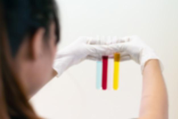 Couleur liquide dans le tube à essai tenir dans la main avec un gant de scientifique isolé sur le mur clair