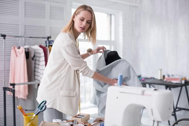 Couleur pastel. tailleur féminin ambitieux touchant le tissu tout en regardant vers le bas