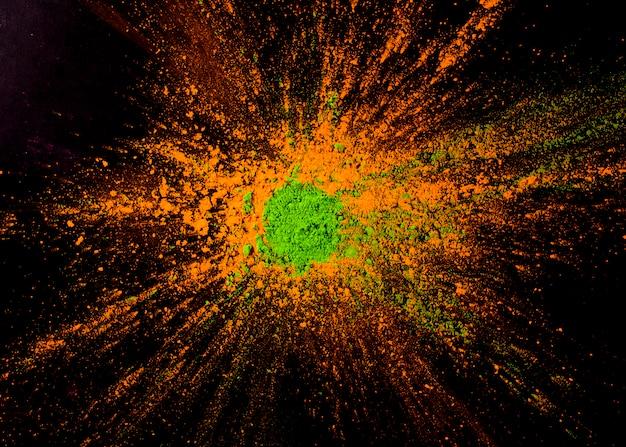 Couleur de poudre verte sur la couleur orange sur le fond noir