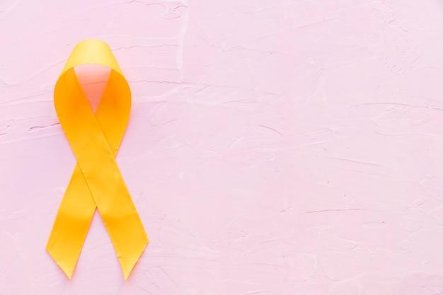 Couleur symbolique de ruban jaune pour le cancer des os de sarcome sur fond rose