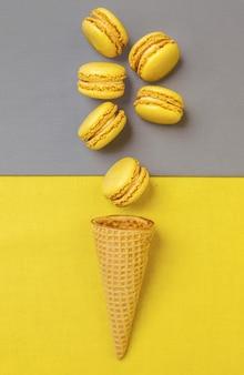 Couleur tendance de l'année 2021. jaune lumineux et gris ultime. macarons jaunes et un cône de sucre sur un mur gris, pose à plat.