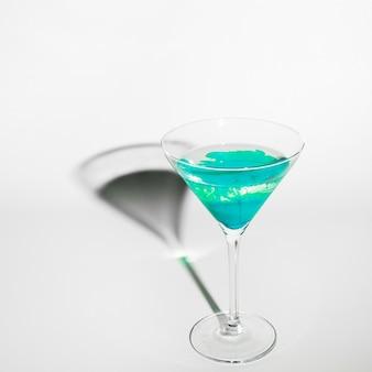 Couleur turquoise diffuse dans l'eau à l'intérieur d'un verre à martini avec ombre sur fond blanc