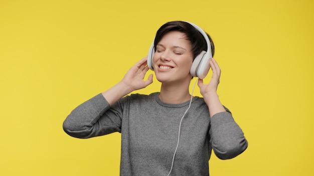 Couleurs de l'année 2021 avec une jeune femme grise ultime et éclairante avec des écouteurs